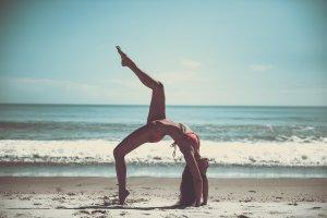 Yoga woman on beach stretching